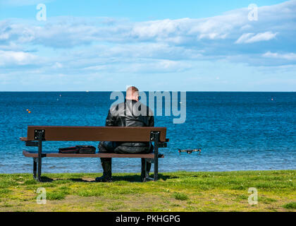 Man in motorbike leathers sitting on bench flying drone, North Berwick, East Lothian, Scotland, UK - Stock Photo