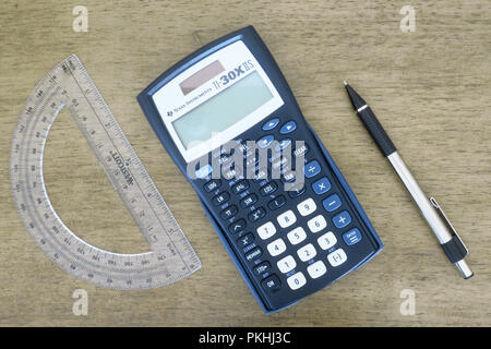 A calculator, protactor, pencil, compass, pen and graph papers laid out on a table. - Stock Photo
