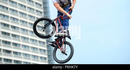 man doing tricks on a BMX bike. BMX freestyle against the backdrop of urban landscape.