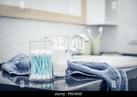 Cotton sticks and cotton pads in transperent conteiner in the bathroom closeup - Stock Photo