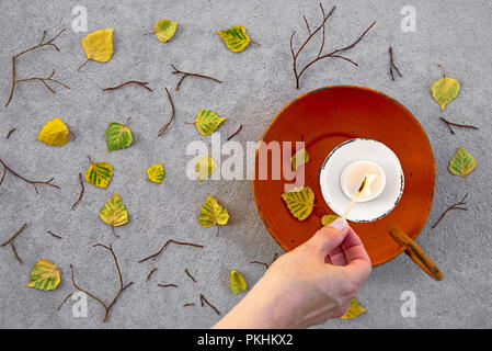Lighting a candle for cozy autumn mood. Fallen leaves and old candleholder on gray concrete background. - Stock Photo