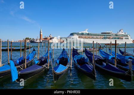 VENICE, ITALY - AUGUST 12, 2017: Big white cruise ship passing near gondolas and San Giorgio Maggiore basilica in Venice in the morning, blue sky in a - Stock Photo