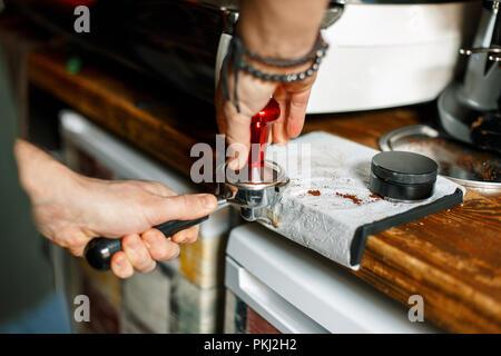 Barista presses ground coffee using tamper - Stock Photo