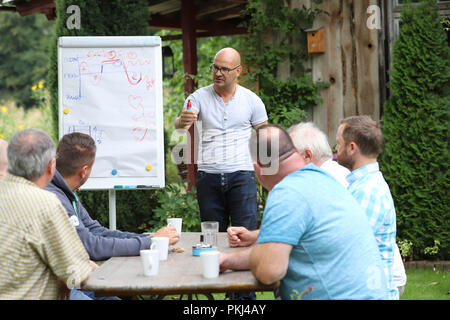 Behavioral trainer during a lecture on 'stress management' in a summery garden in Brandenburg / Germany. - Stock Photo