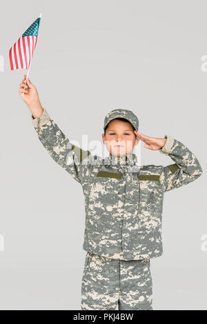 portrait of boy in camouflage clothing saluting while holding american flagpole in hand isolated on grey - Stock Photo