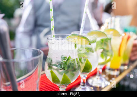 Bartender makes cocktail mojito. Misted glass, selective focus. Alcoholic beverage based on bar counter with ice cubes and lyme. outdoor party - Stock Photo