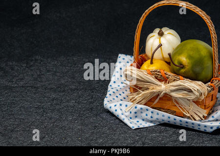 Pears in a straw basket. Napkin with star pattern. Black background, isolated. Concept for fall and autumn - Stock Photo