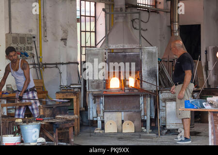 Two glass makers in the Guarnieri Glass Factory, Murano, Venice, Veneto, Italy working at the furnaces - Stock Photo