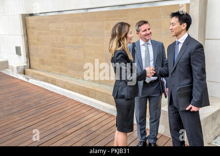 A group of executives shaking hands in their office building - Stock Photo