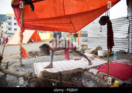 Naga baba sadhu doing yoga at nashik Kumbh Mela maharashtra India - Stock Photo