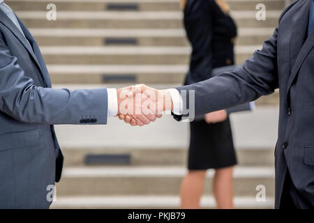 Professional handshake with female colleague in the background - Stock Photo