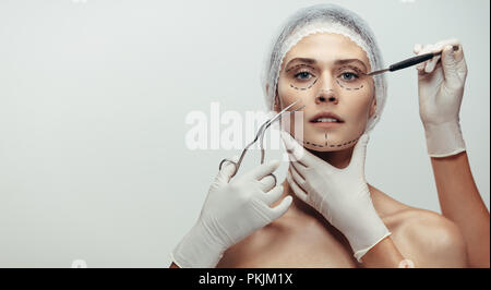 Horizontal shot of woman under going a face lift surgery. Female face with dotted line drawn and beautician holding surgical instruments on grey backg - Stock Photo