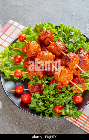 baked in tomato sauce meatballs with fresh tomatoes on a bed of lettuce leaves on a black plate on a concrete table,  vertical view from above - Stock Photo