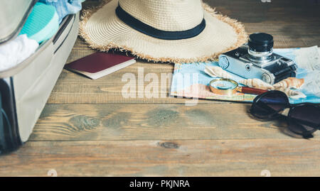 Open suitcase with female clothes for trip. Packing things. - Stock Photo