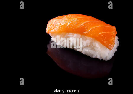 Macro shot of one sushi with salmon on black backgorund with its reflection - Stock Photo