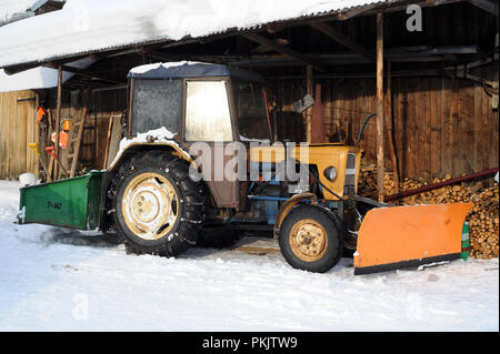 Tractor with snow plough attachment in Bukowina Tatrzanska in the Tatra Mountains in in the south of Poland, - Stock Photo