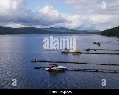 Boats docked on a lake in the Adirondack mountains of New York state - Stock Photo