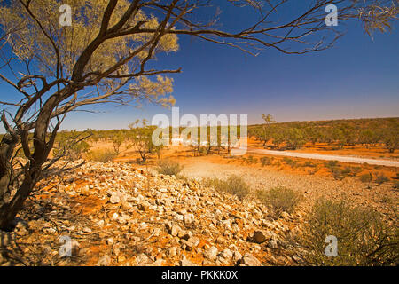 View from stony hill of Australian outback landscape with road slicing across plains, dotted with trees, that stretch to horizon under blue sky in Qld - Stock Photo