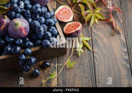 Fresh Black Grapes and Figs in Dark Wooden Tray on Wooden Table Selective focus - Stock Photo
