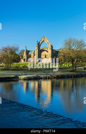 Blue sky & scenic priory ruins of Bolton Abbey reflecting in River Wharfe on frosty day - Yorkshire Dales countryside, North Yorkshire, England, UK. - Stock Photo