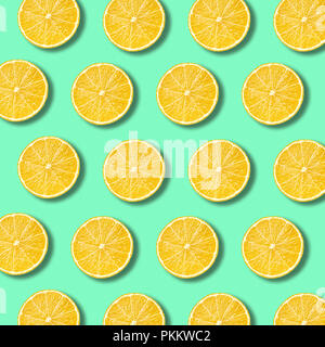 Lemon slices pattern on light vibrant green color background. Minimal flat lay food texture - Stock Photo
