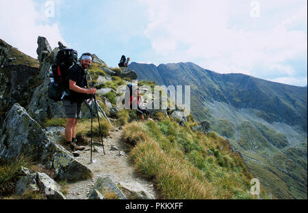 Hikers in the Fagaras Mountains in Transylvania Romania. The countrys highest mountain Mount Moldoveanu in the background. September 2005. - Stock Photo