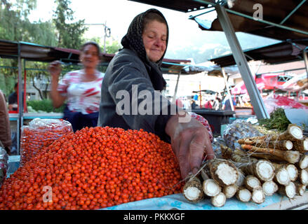 Woman selling berries and horseradish root in the market in Sibiu in Transylvania Romania. September 2004 - Stock Photo