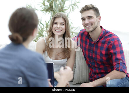 Young happy couple at therapy session with family psychologist - Stock Photo