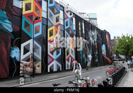 A hipster cycling on a bike past a big street art mural painting in New Inn Yard Shoreditch near Hackney in  East London UK  KATHY DEWITT - Stock Photo