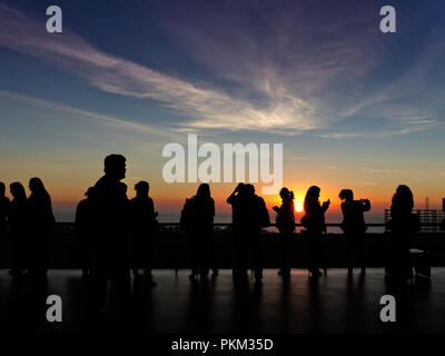Silhouette of a group of people having a rest during a congress with the sunset in the background several of them taking pictures with cell phones - Stock Photo