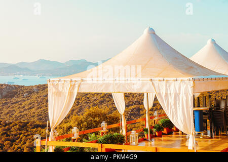 Idyllic sunrise at cafe in Costa Smeralda in Sardinia in Italy. Mediterranean Sea on the background - Stock Photo