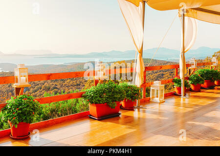 Idyllic sunrise at cafe on Costa Smeralda in Sardinia, in Italy. Mediterranean Sea on the background - Stock Photo