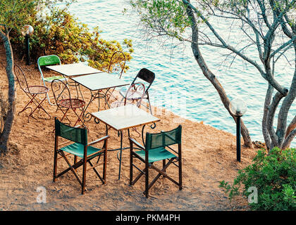 Street cafe in Costa Smeralda in Sardinia in Italy. Mediterranean Sea on the background - Stock Photo
