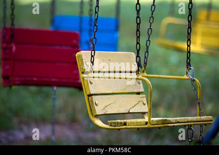Close-up of empty wooden painted blue, yellow, vintage seats chairs of multi-colored carousel hanging on chains outdoor in city amusement park on sunn - Stock Photo