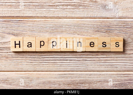 Happiness word written on wood block. Happiness text on table, concept. - Stock Photo