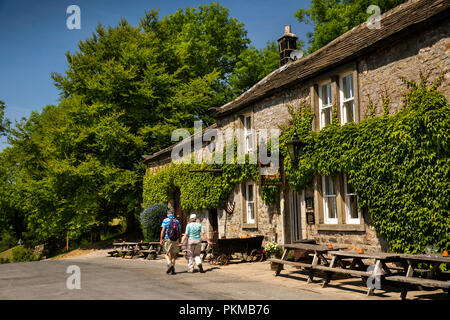 UK, Yorkshire, Wharfedale, Appletreewick, senior walkers passing Craven Arms public house - Stock Photo