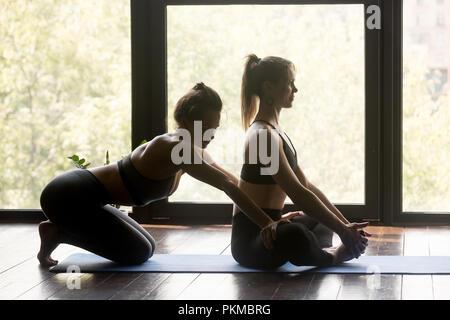 Young sporty female yoga teacher teaching yoga student - Stock Photo