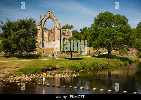 UK, Yorkshire, Wharfedale, Bolton Abbey, stepping stones over River Wharfe below Augustinian Priory ruins - Stock Photo