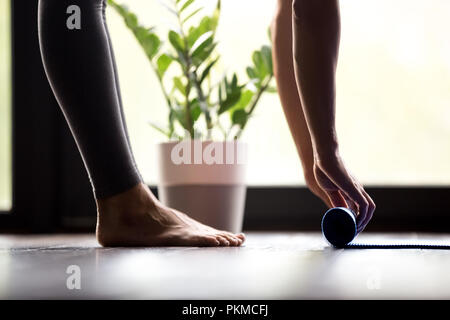 Woman unrolling yoga mat, close up view - Stock Photo