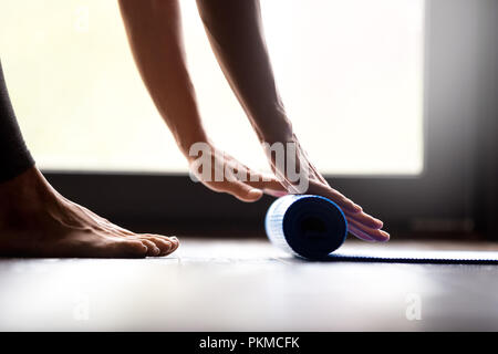 Young woman rolling fitness mat, hands close up  - Stock Photo