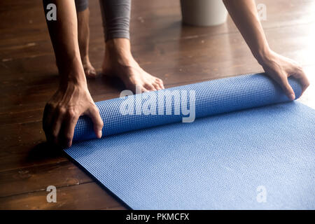 Time for practice, female hands unrolling blue yoga mat - Stock Photo