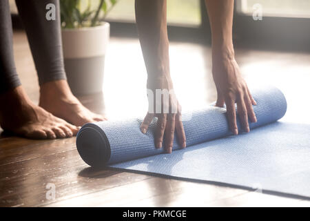 Woman unrolling blue yoga mat, legs close up - Stock Photo