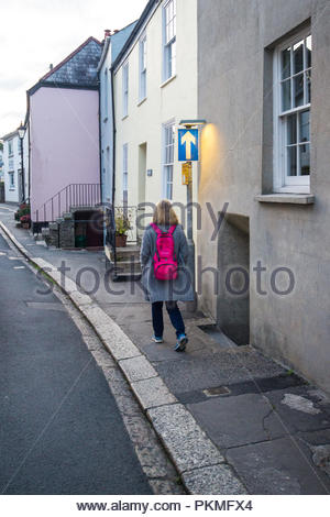 Woman with blond hair and a pink rucksack walking along a pavement past a blue one way street sign. - Stock Photo