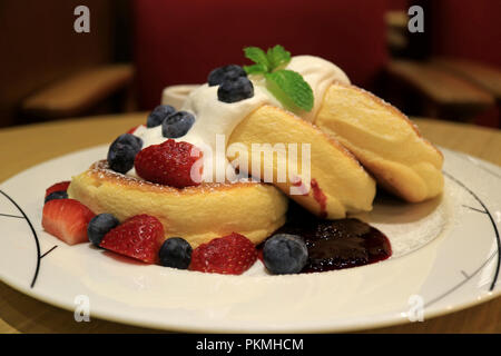 Mouthwatering Fluffy Souffle Pancake with Fresh Whipped Cream and Mix Berries Served on white Plate - Stock Photo