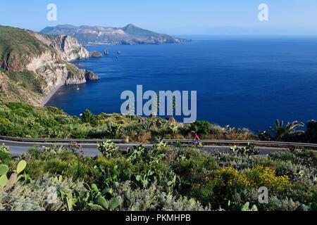 Cyclist on the Belvedere Quattrocchi with a view over the rocks Faraglione on the island Vulcano, Pianoconti, Lipari - Stock Photo