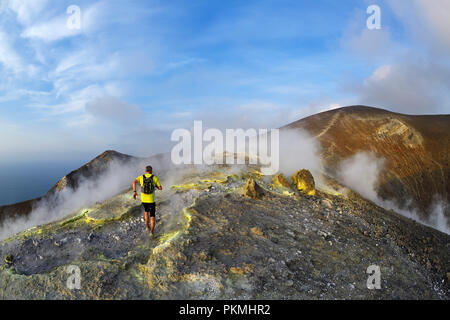 Trailrunner surrounded by sulfur fumaroles and chloride crusts on the crater rim, Gran Cratere, Vulcano Island - Stock Photo