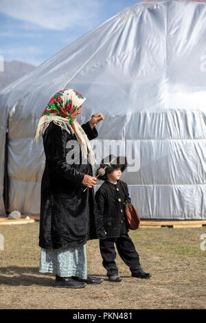 Lake Issyk-Kul, Kurgyzstan, 6th September 2018: local boy in Kyrgyz outfit with his grandmother during World Nomad Games 2018 - Stock Photo