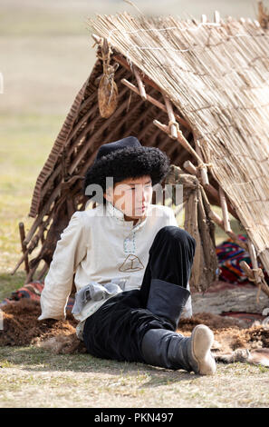 Lake Issyk-Kul, Kurgyzstan, 6th September 2018: local boy in full Kyrgyz outfit during World Nomad Games 2018 - Stock Photo