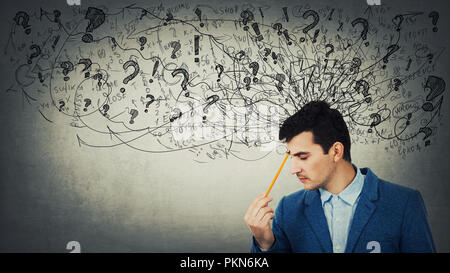 Thoughtful stressed young man with a mess in his head closed eyes pointing pencil to forehead. Anxiety and headache feeling. - Stock Photo