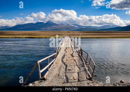 Shabby wooden bridge over a river with distant mountain range in background, Altai Mountains, Western Mongolia - Stock Photo